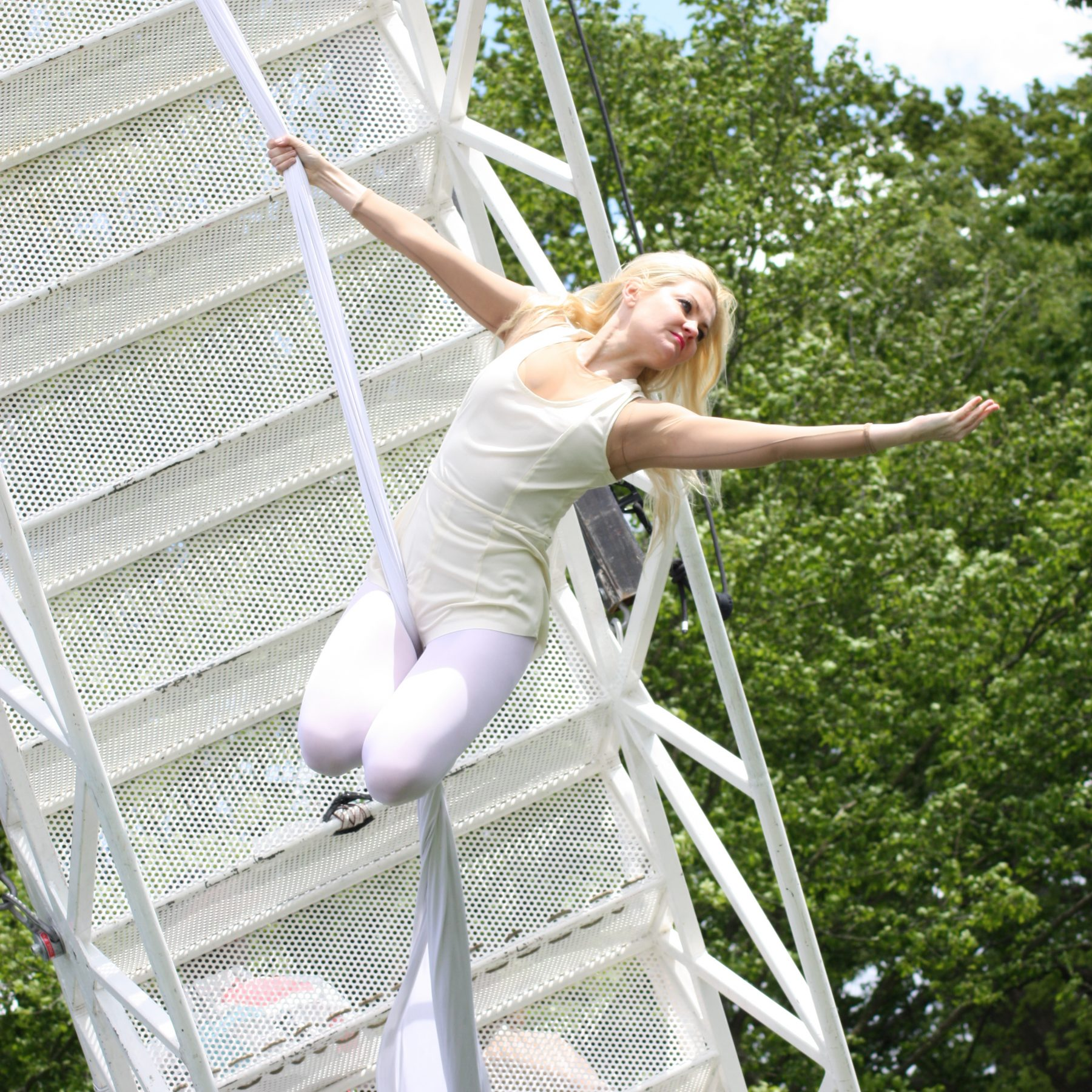 Karina wearing white, swings from a white aerial silk, her blonde hair flying and arm outstretched. The Weighting show bridge is behind her.