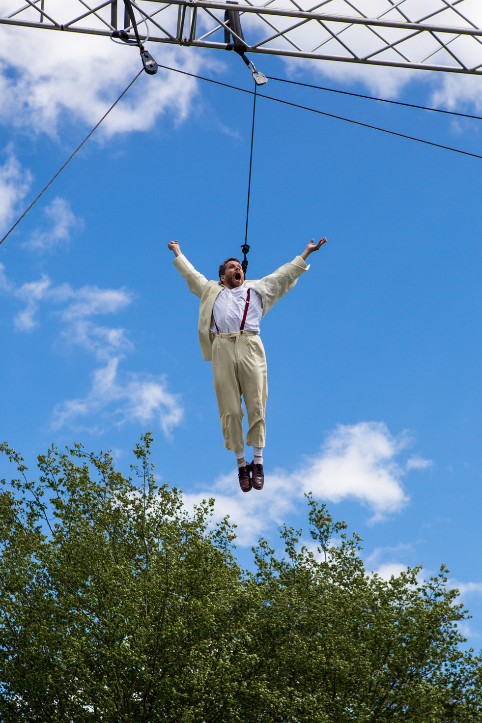 Jamie flies on a harness, his arms outstretched in joy, a bright blue sky behind him.