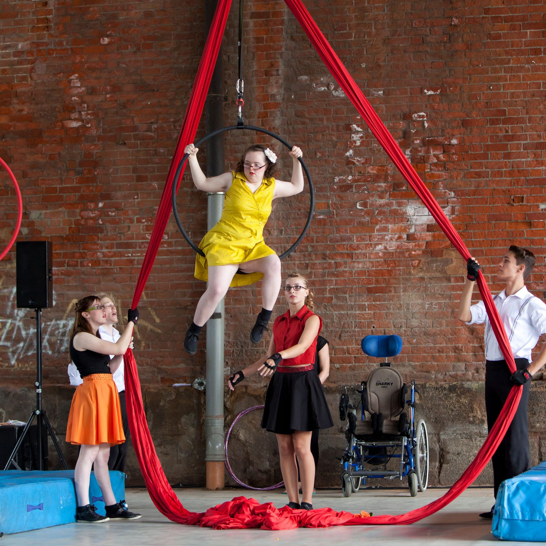 A young integrated group of circus performers wear bright colours as they perform their show. A girl hangs from an aerial hoop whilst two others hold red aerial silks.