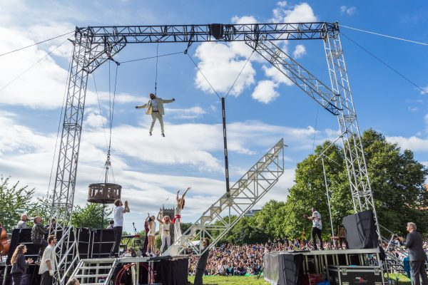 Weighting show in Castle Park. Jamie Beddard flying from large rig. Cast celebrate below, stretching arms up towards him. Large crowd watching show.