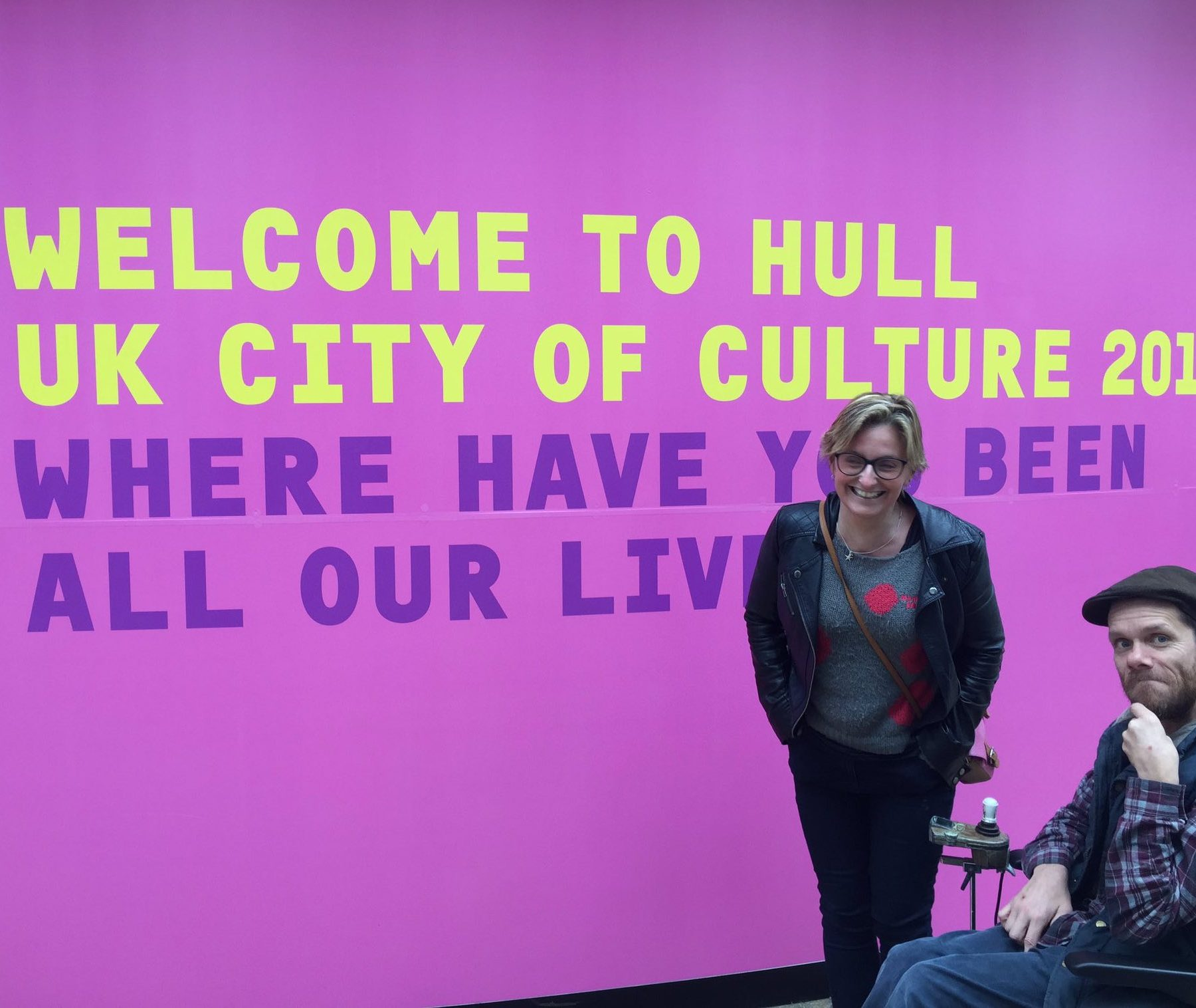 Jamie and Claire in front of a big purple sign that reads 'Welcome to Hull UK city of culture 2017. Where have you been all our lives?'
