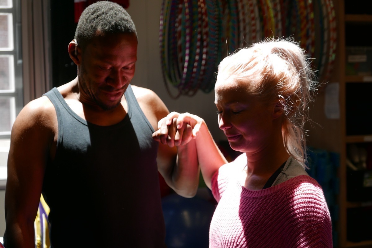 David hold hands with a female performer from Circus Oz. They both have their eyes closed and heads bowed, smiling as sun bathes them through the window.
