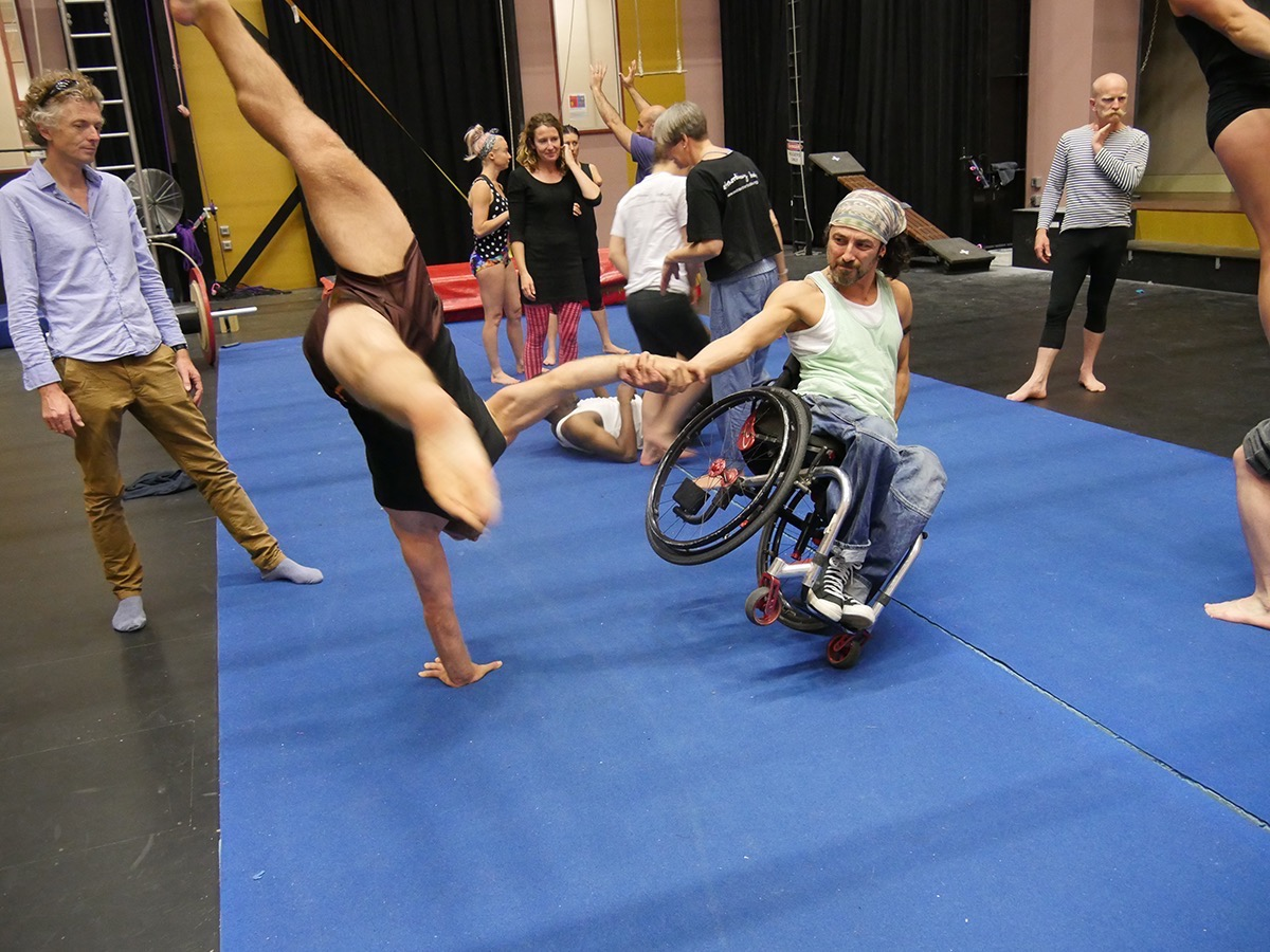 Dergin dances with his wheelchair, leaning over dynamically whilst holding the hand of an artist doing a handstand.