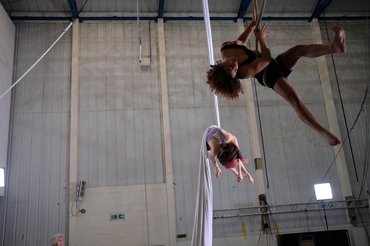 Extraordinary Bodies: Two female aerialists, one black with brown afro hair and the other visually impaired with red hair swing from the ceiling, their limbs flying in all directions as the dance on their aerial equipment.