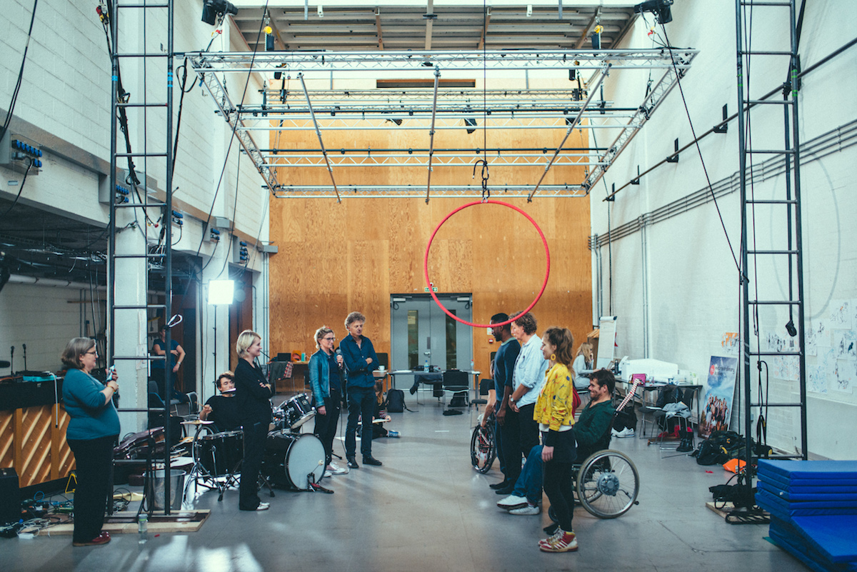 Extraordinary Bodies artists form 2 lines in the National Theatre Studios. A red aerial hoop hangs above their heads from circus rigging. Claire holds a microphone, Jonny is set up at the drums.