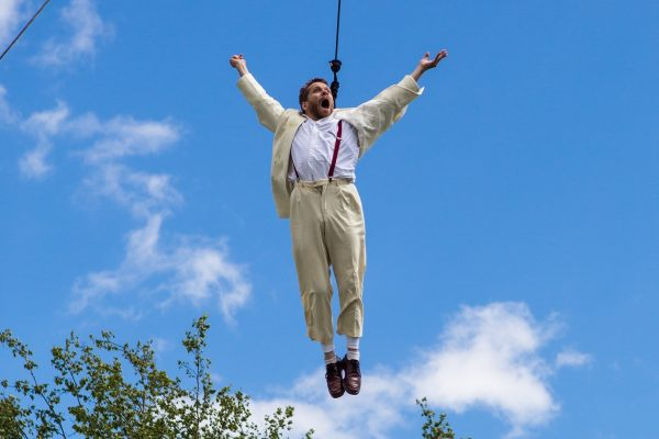 Jamie flys in the air on an aerial harness, his arms outstretched with an ecstatic expression on his face, a bright blue sky behind him.