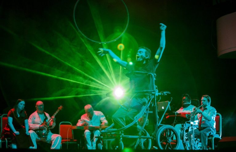 Dave Young sits in his wheelchair on stage, with green staging light bursting behind him. His arms are in the air and mouth wide open. The British Paraorchestra sit behind him playing instruments.