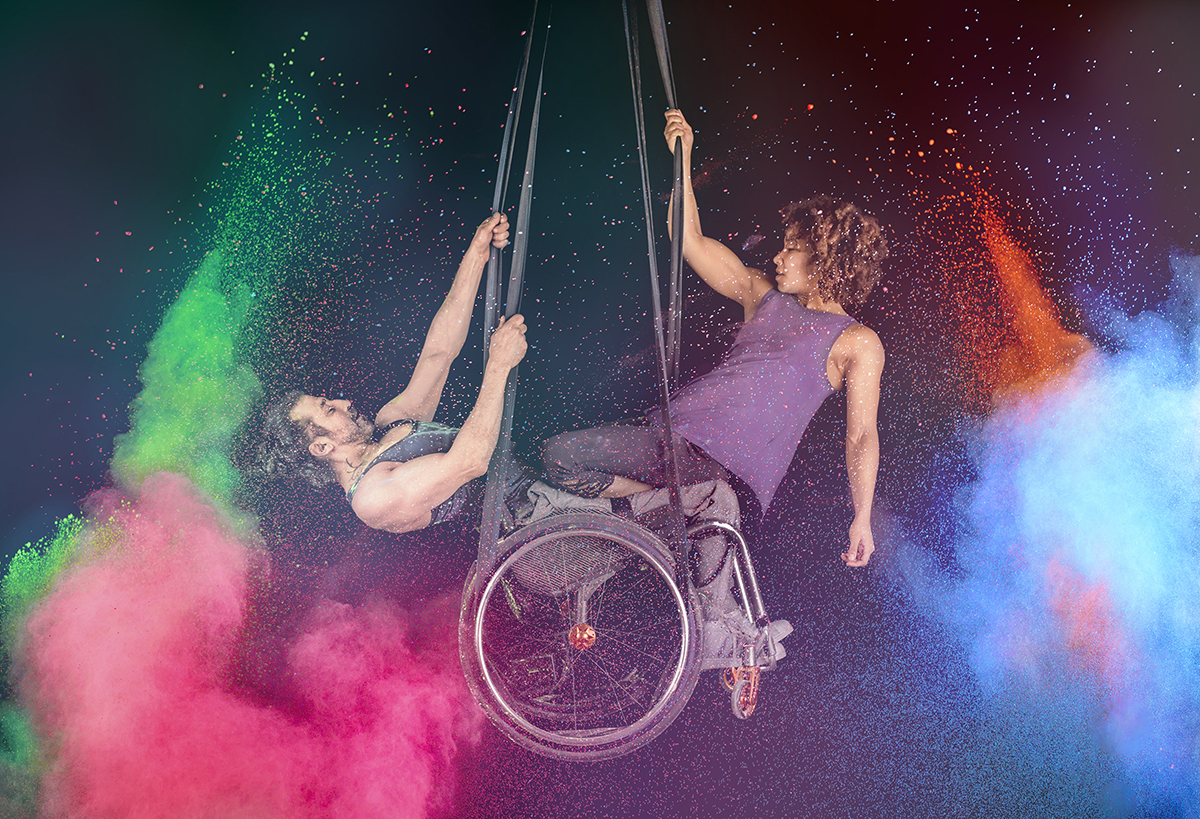Suspended from the ceiling and surrounded by explosions of colourful chalk, two performers sit in a wheelchair, their muscly arms revealed