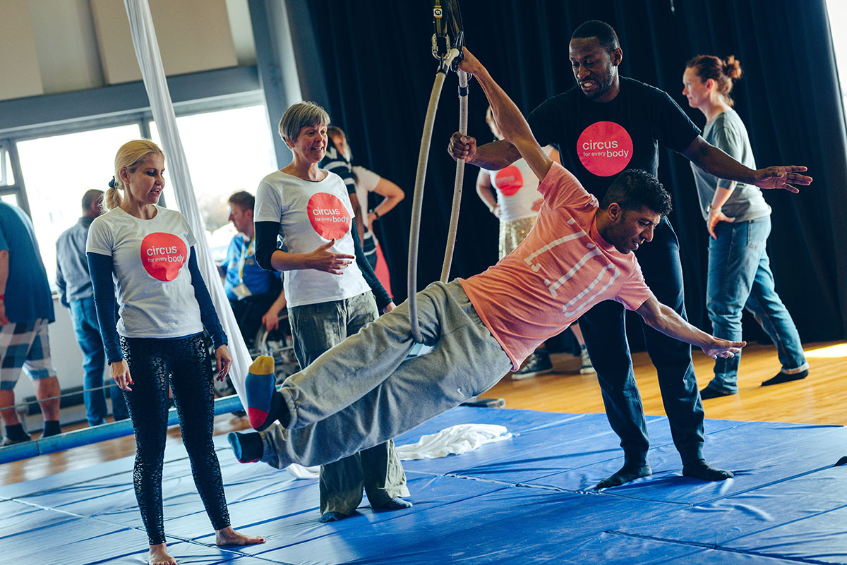 A man hangs off an aerial hoop in an Extraordinary Bodies workshop, three workshop leaders stand behind him wearing t-shirts saying 'Circus for Every Body' smiling and encouraging him