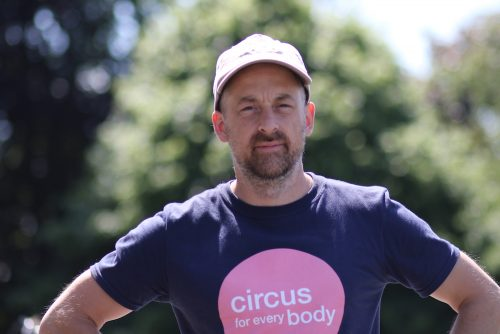 Headshot of Will Datson, a white man with dark stubble facial hair, wearing a 'circus for every body' tshirt and a cap.