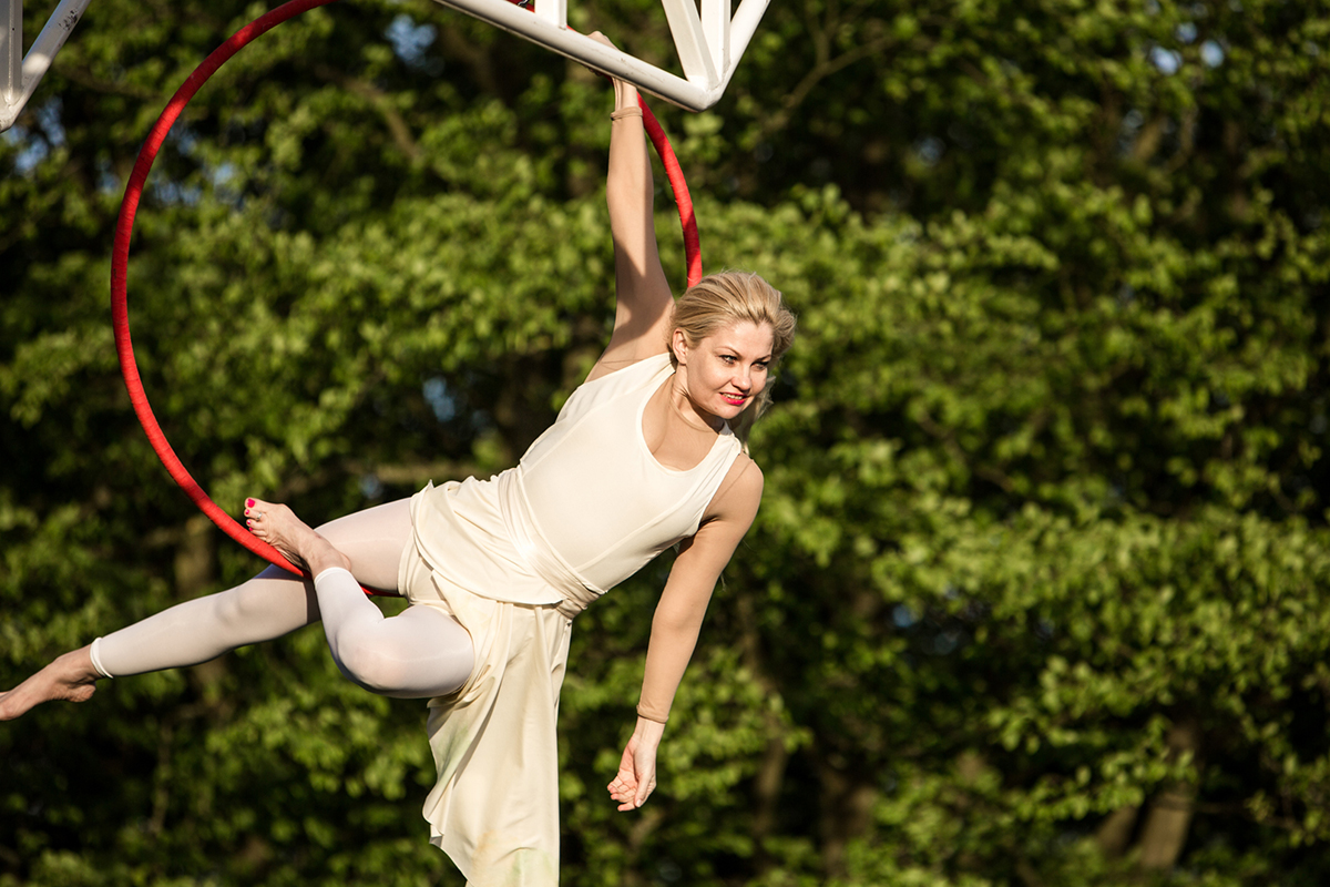 Karina Jones swings on a red aerial hoop in the Weighting show Southwark 2015