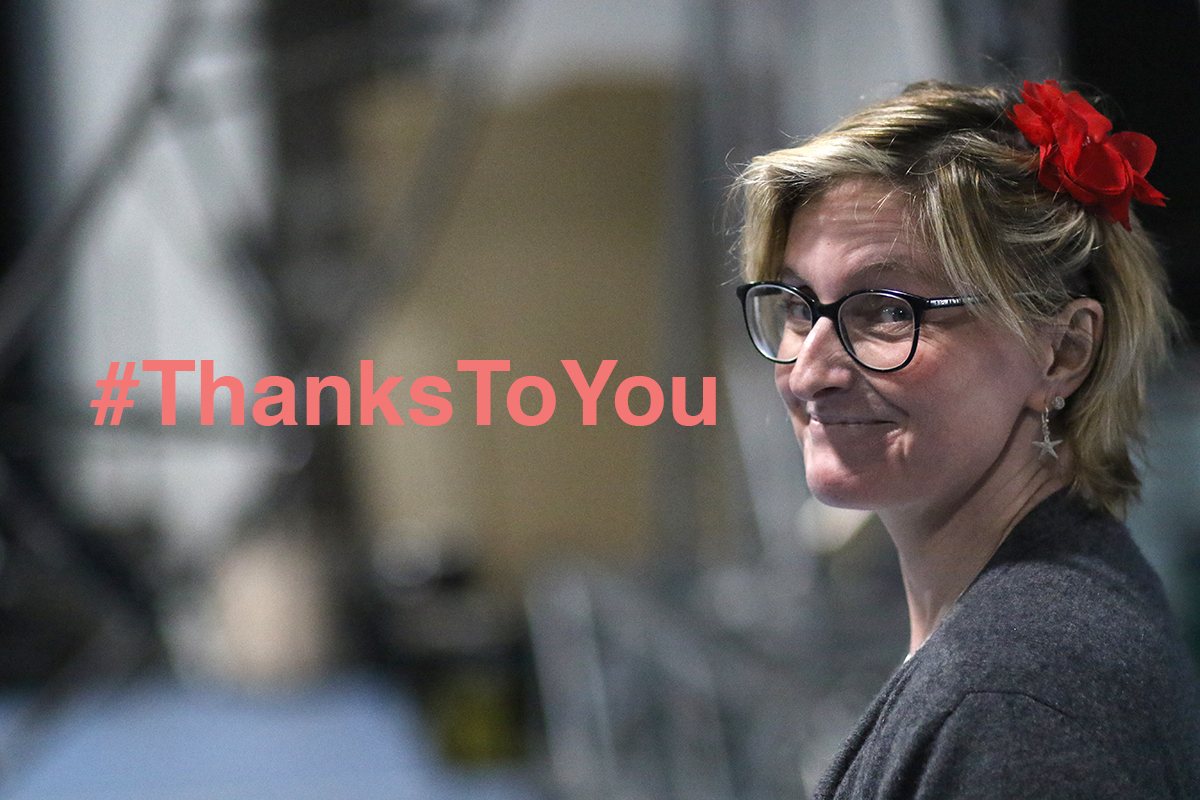 Co Artistic Director Claire Hodgson turns to the camera smiling, a red flower in her blonde hair. Text reads #ThanksToYou
