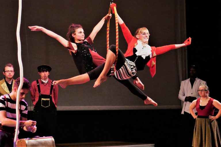 Extraordinary Bodies Young Artists: Two young aerialist sit in an aerial hoop on stage their arms outstretched. They are wearing red, white and black. The other cast members watch them from onstage.
