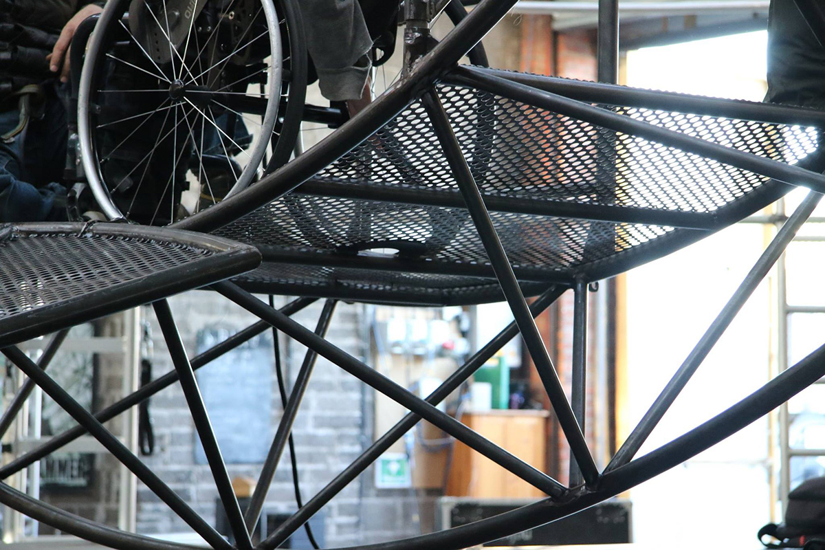 Closeup of wheelchair on curved metal structure