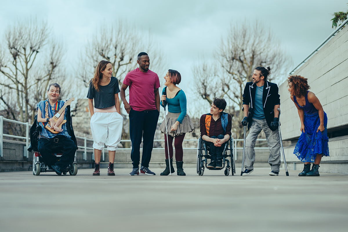 Seven artists line up outside standing on grey concrete. They wear colourful clothes and look towards each other laughing. Two of the cast are in wheelchairs, one holds a stick and one holds crutches. They are a mix of male female, black, white and mixed race, disabled non-disabled.