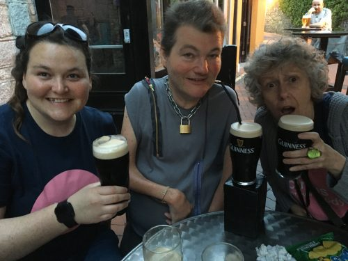 Eilis, Joh and Spicer sit at a table in an Irish pub holding pints of Guinness and grinning