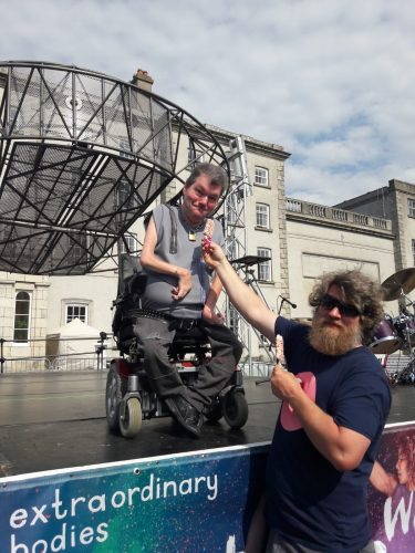 John Kelly sits on an outdoor stage in his wheelchair whilst Dave the production manager passes him an Ice Lolly covered in colourful sprinkles
