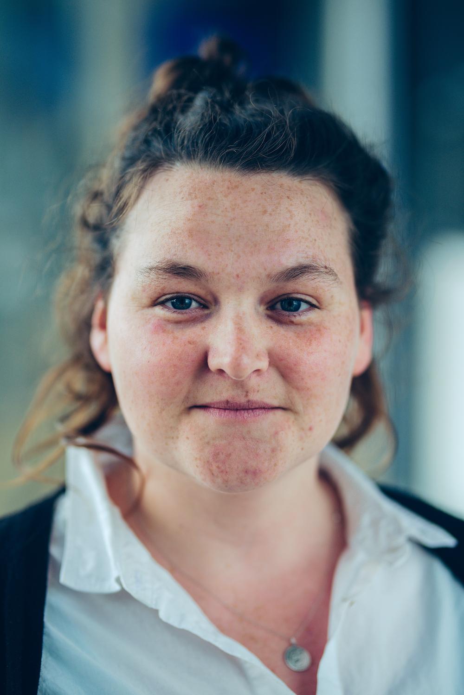 Eilis Davis, smiling to camera - Eilis has long, wavy, dark brown hair tied up. A gentle smile, lots of freckles and deep blue eyes.