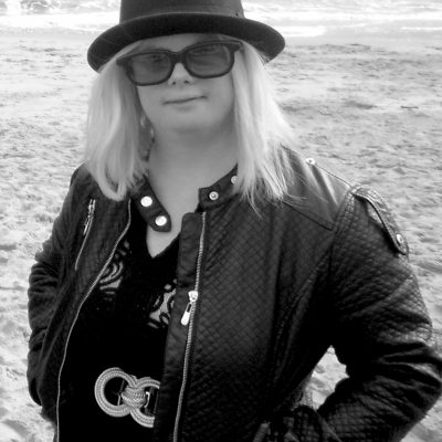 Headshot of Helen Cherry, a white woman with shoulder length blonde hair. She wears a black bowler hat and sunglasses