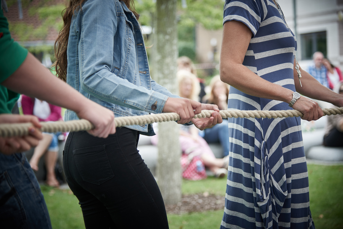 Close up of a group of people in a row, their hands holding a rope.