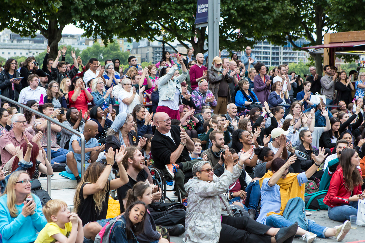 An audience outside at The National Theatre, cheering and applauding with smiles - Extraordinary Bodies performance What Am I Worth