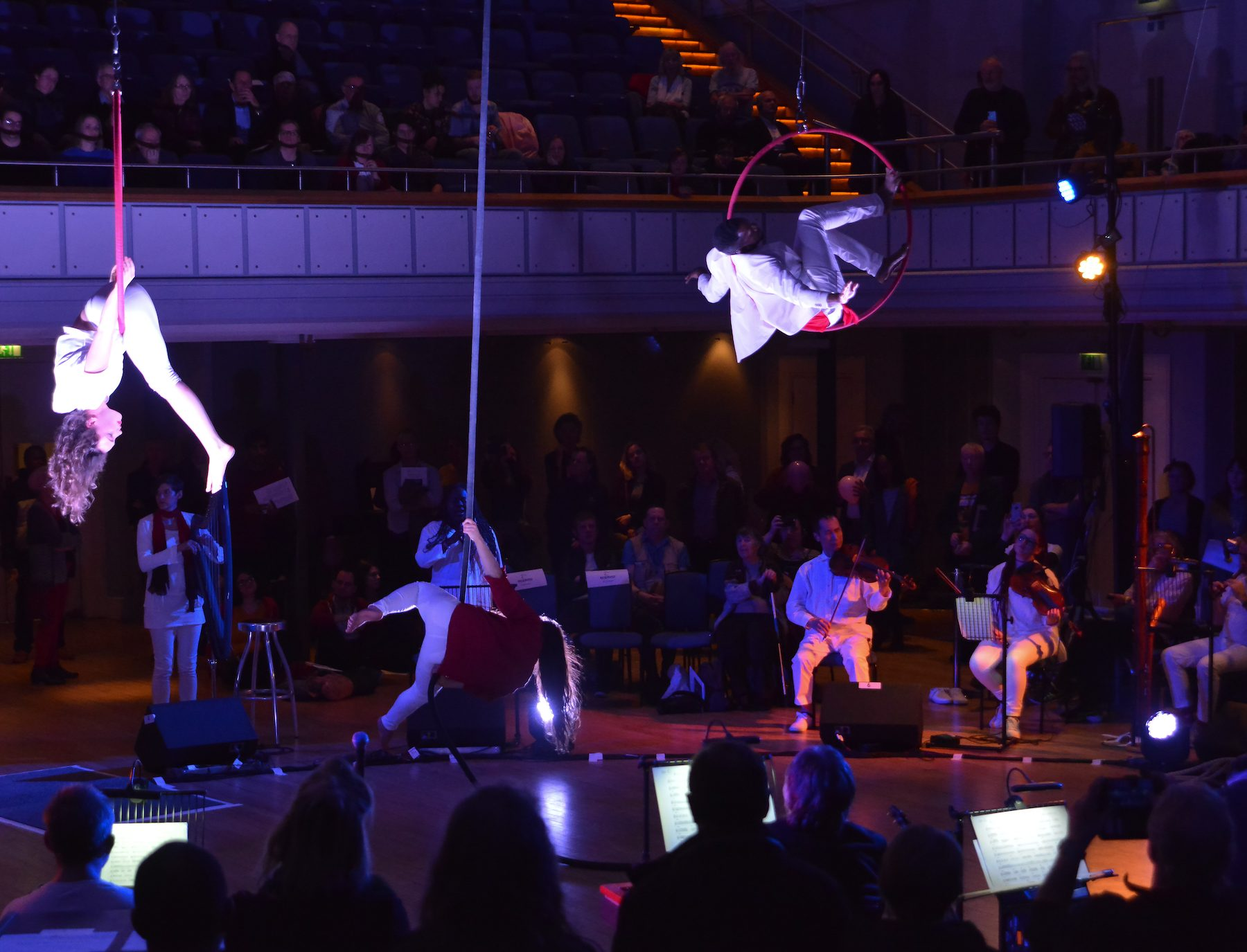 Wide shot of Birmingham Town Hall, the musicians seated in a large circle around the room, creating a centre stage for the aerial artists. One girl suspended upside down in a red hoop, another man perches with his legs high, sat in another red hoop. A second girl is flowing down a rope, also suspended from the ceiling