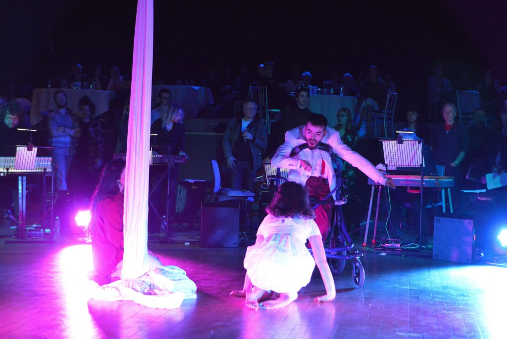 Dave Young moves across the stage in his walker, a girl crouches on the floor in front of him. Another girl sits at the bottom of the silks to their left. The corner of the stage is illuminated with pink light.