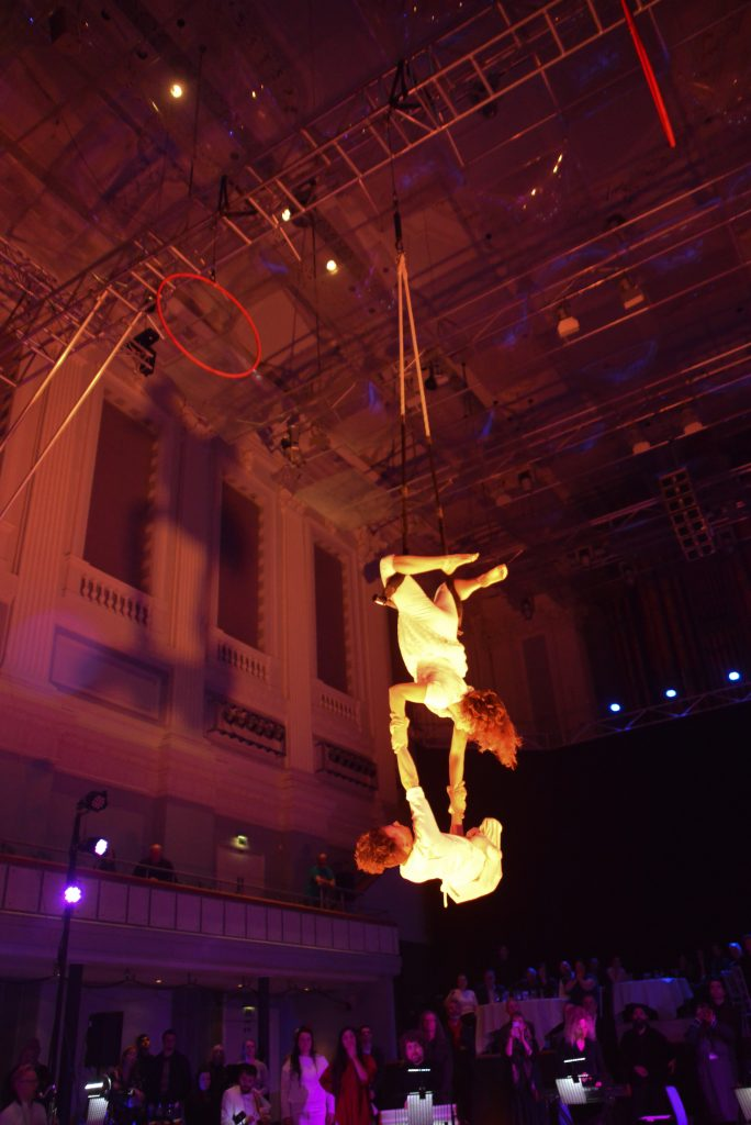 An aerialist is suspended from a trapeze from her legs, the large ceiling of Birmingham Town Hall towers up above. She holds a man by the strength of his arms, dangling above the musicians.