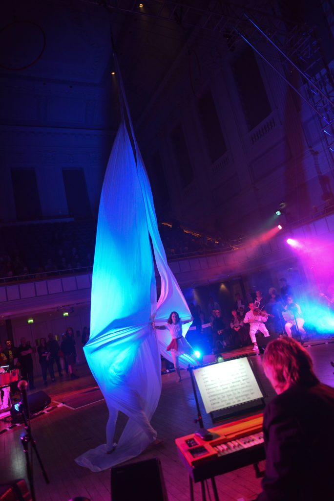 Artists create a spectacle in the centre of the large town hall, as the silks billow into large sails, illuminated by bright blue light. Musicians of the Paraorchestra surround them in a large circle.