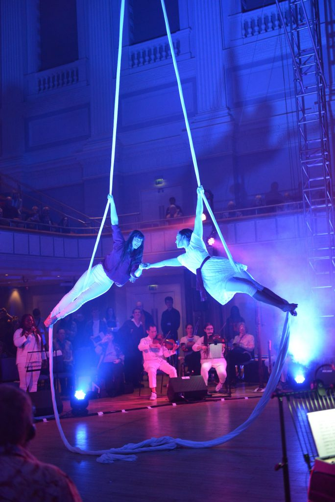 Two female aerialists suspended from silks in the centre of the floor stage. Their arms outreached and hands touch.
