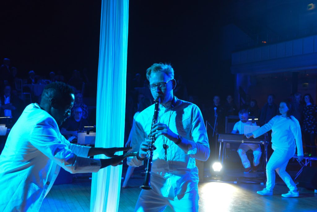 A man playing the clarinet walks across the central stage space, silks illuminated in bright blue light behind him. Another man moves around him to the rhythm with arms outstretched.
