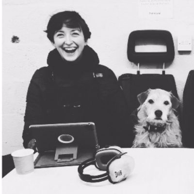 Photograph of Georgina, laughing to camera. She's a white woman, with short dark hair. She's sat next to a small scruffy light haired dog.