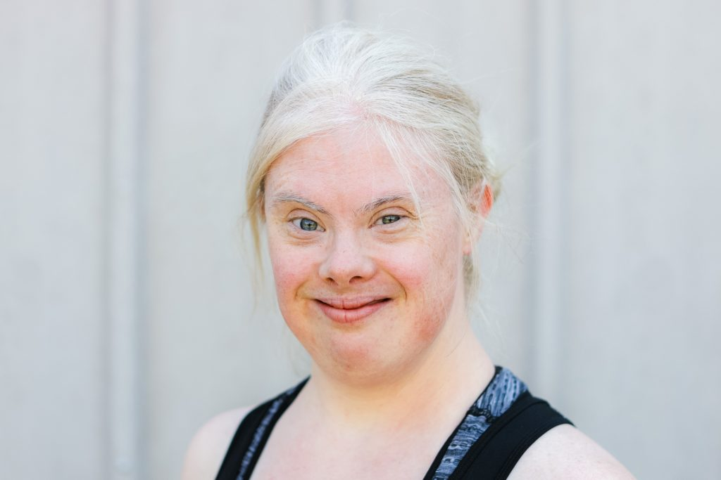 Helen poses for the camera. She is a young white woman with bleached blonde hair tied back. She has bright blue eyes and is wearing a sporty sleeveless top.