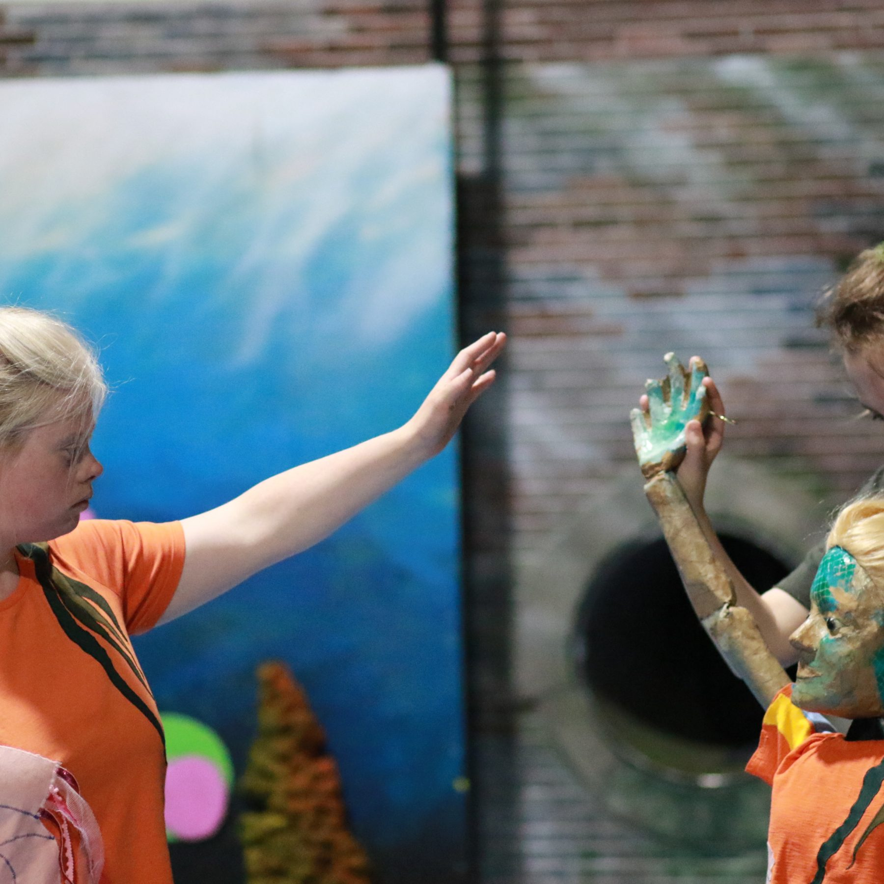 Splash!, by Extraordinary Bodies - Flo, a young learning disabled girl (played by Helen Cherry) reaches her arm up to reach a puppet version of herself, who is mirroring her.