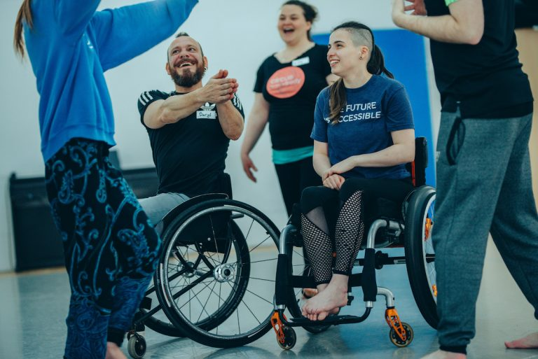 Extraordinary Bodies Young Artists moving around a rehearsal room. One of the young theatre members is a wheelchair user; her tshirt reads 'THE FUTURE IS ACCESSIBLE'