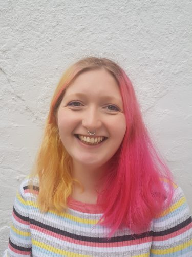 Ellie Stephens, smiling to camera - a young white girl, with long shoulder length hair - one side yellow blonde and the other side dyed bright pink. Ellie smiles. Her septum nose piercing is just visible.