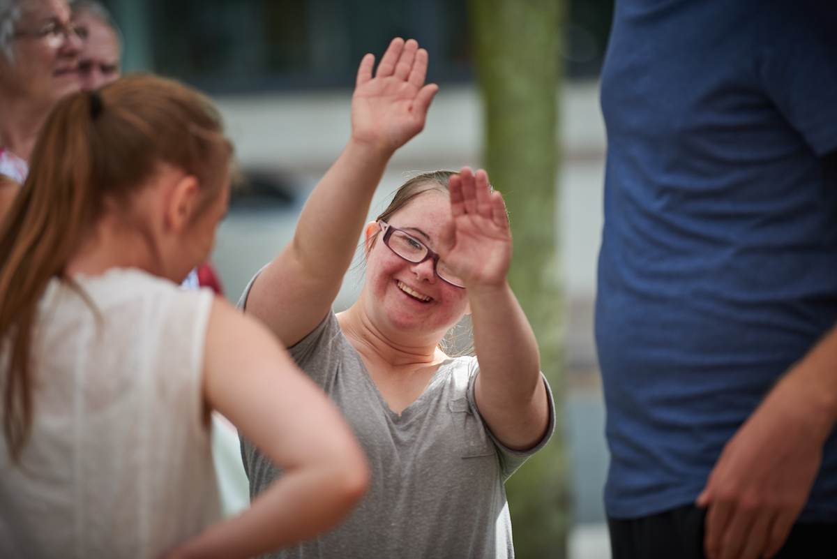 Jess, a young girl with Downs Syndrome, waving to camera with both arms in the air, smiling.