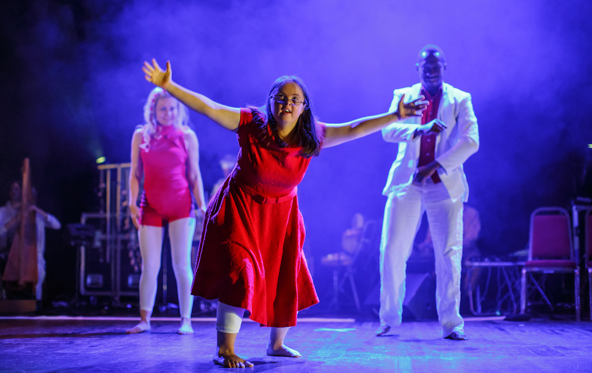 Extraordinary Bodies performing on stage with British Paraorchestera; a learning disabled woman stands centre stage, lunging forward with her arms outstretched. She wears a long, bright red dress. The stage lighting is a moody purple. Two more artists move in the background.