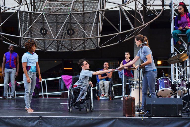 Extraordinary Bodies perform What Am I Worth? at London's National Theatre Riverstage Festival. Jonny is centre stage in his wheelchair; reaching out to Aislinn's hand to take a piece of paper. The rest of the artists look on with concerned expressions and frowns.