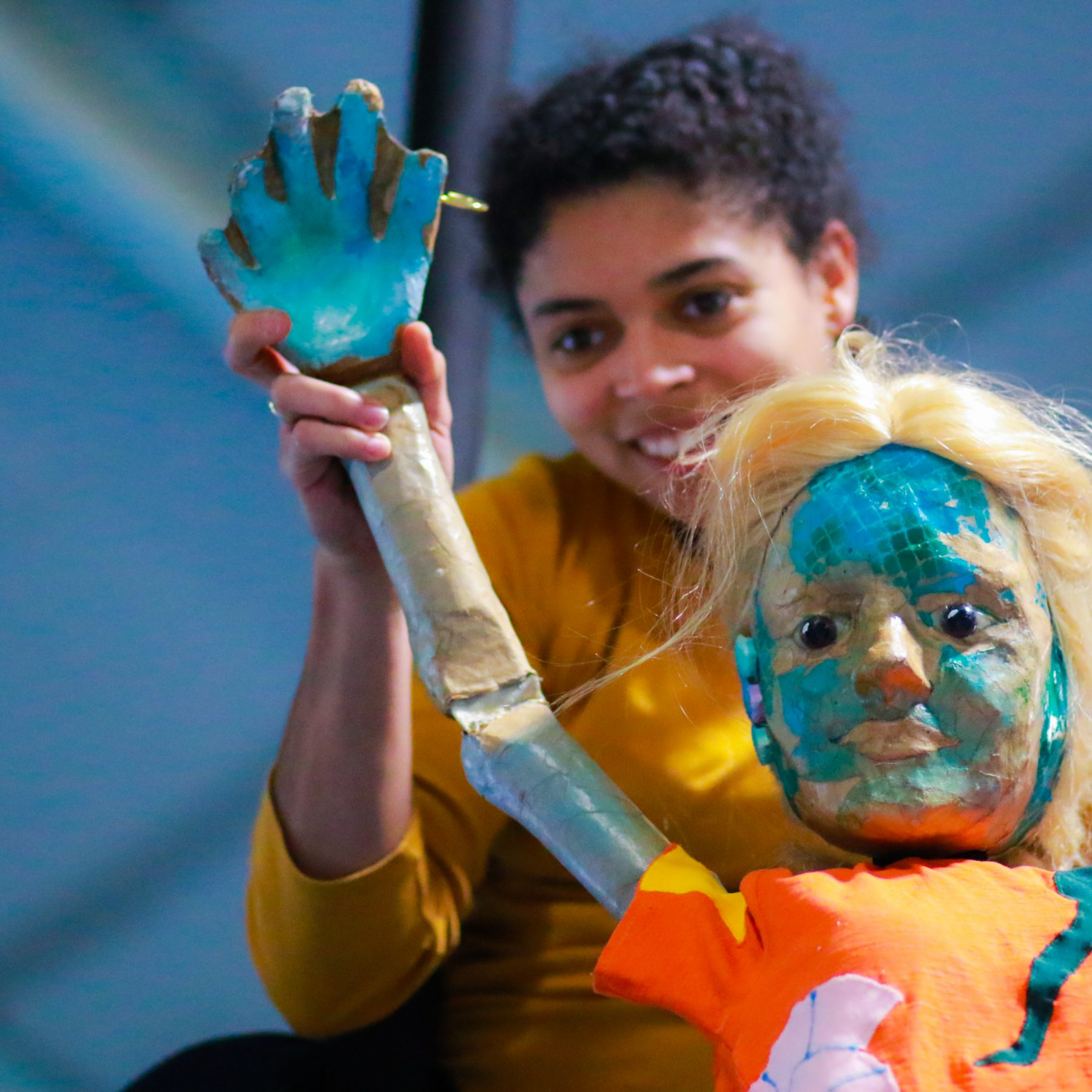 A young mixed-race woman is smiling and holding up a puppet of a girl with blond hair, an orange top and fish-like turquoise scales of her face.