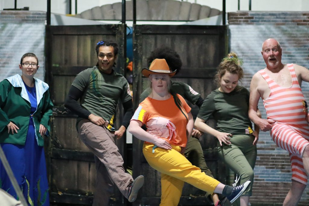 The cast line dance with Helen Cherry as Flo in the middle wearing a cowboy hat.