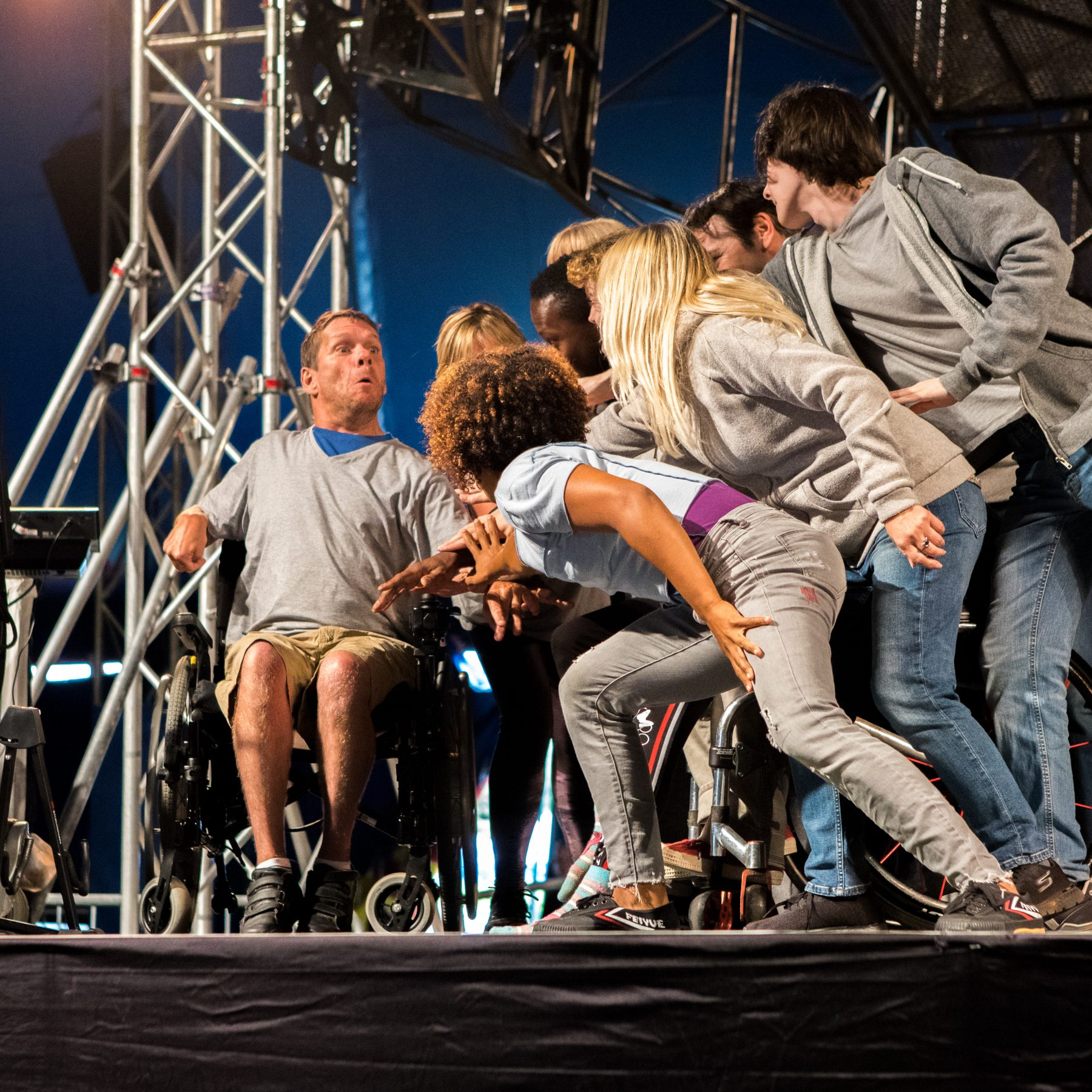 A man in a wheelchair looks surprised while a group of performers lean over him. Musicians on the left and a giant steel wheel in the background.