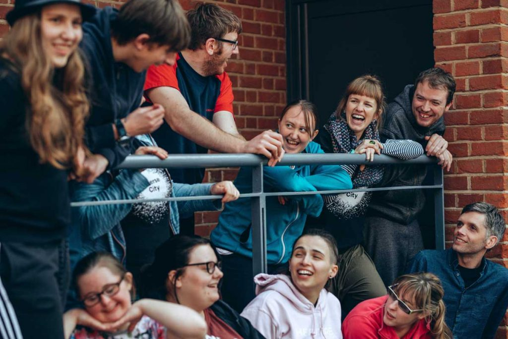 A group of disabled and non-disabled young people and adults laughing together, outside a red brick building, interacting with one another.