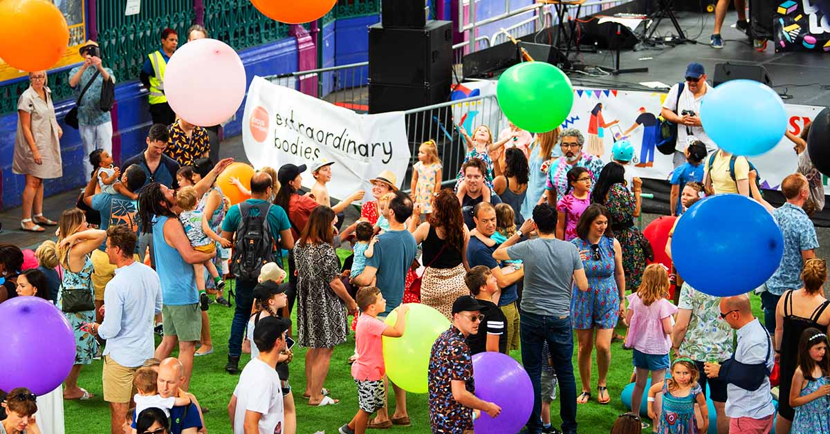 """A crowd of people at an outdoors event. Colourful giant balloons flying in the air. A large white banner with a light red circle and black logo that reads: """"Extraordinary Bodies""""."""