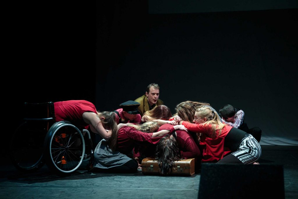 A group of young disabled and non-disabled people grouped together in the centre of a dimly lit stage. They are all sitting or bending their bodies towards the ground, holding onto each other.