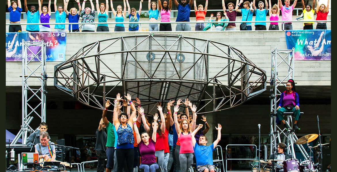 A diverse group of performers stand and sit in their wheelchair on an outdoors stage. They all raise their hands up in the air in celebration. In the background, a giant steel wheel. Above it, on a balcony more young people stand in a line, raising their hands in celebration too.