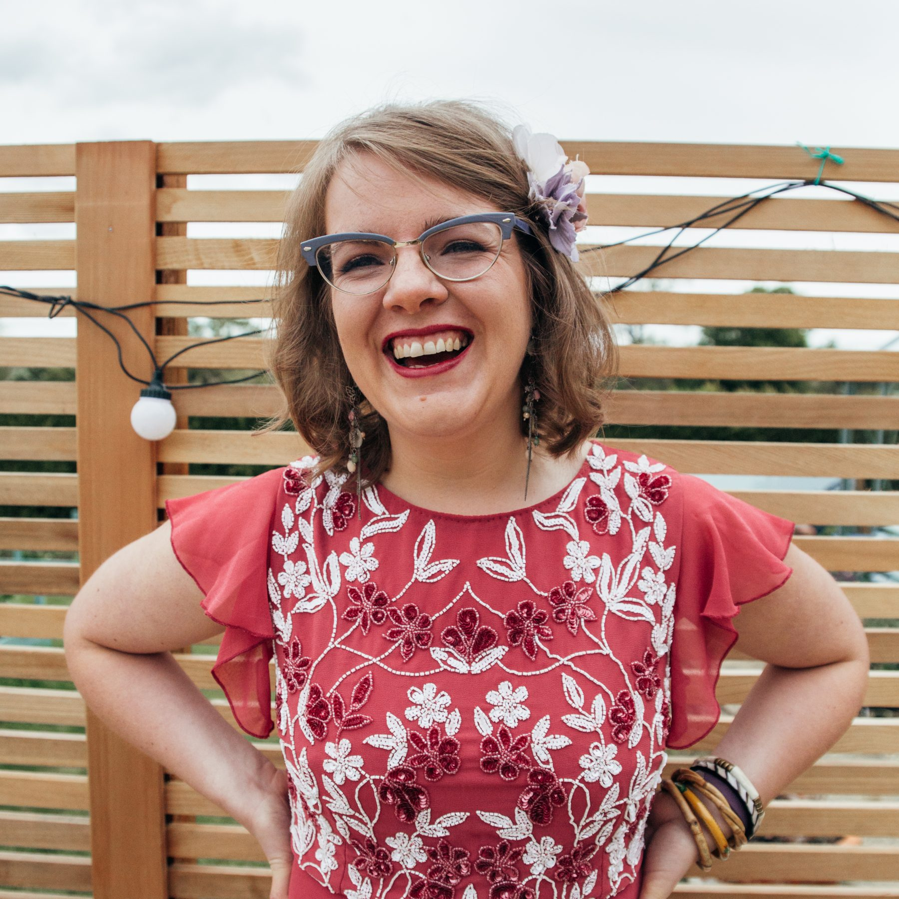 Kate is smiling brightly for the camera, her hands on her hips. She wears vintage librarian-style glasses, a flower in her hair and a bright red, blue and black flowery top.