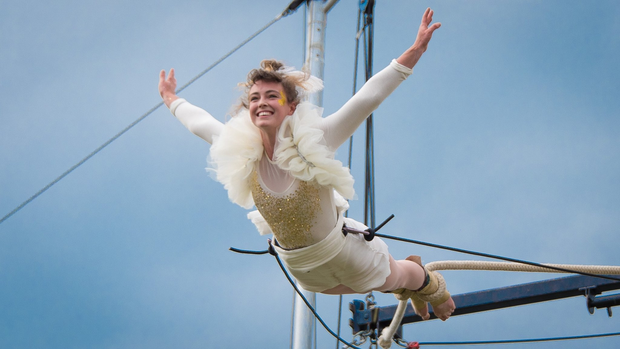 Tilly flies through the air, smiling brightly, her feet tied to a circus rope. Outdoors rigging and a grey sky behind her.