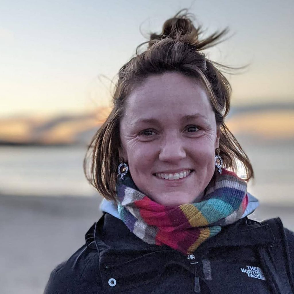 Jodie - shoulder-length brown hair, a bright smile, a colourful scarf. She is standing on a beach, with a sunset and sea in the background.