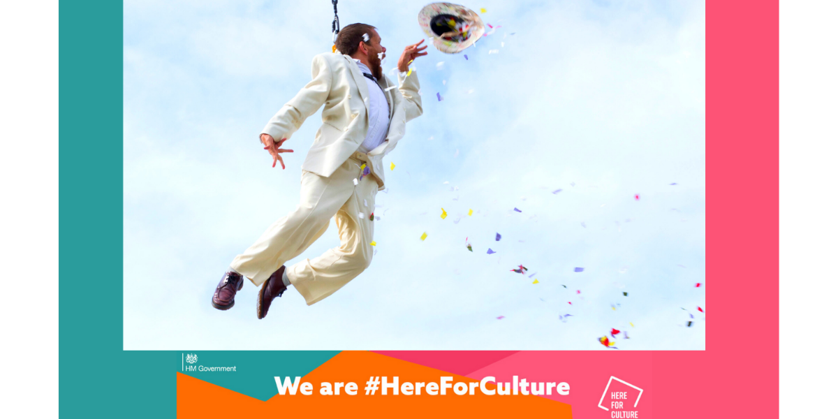 "A man flying through the air, held by a harness. Colourful confetti flying out of his hat which he holds in his hand. ""We are #HereForCulture"" at the bottom."